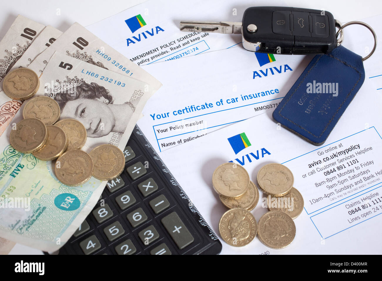 Motor insurance certificate alongside money, keys and calculator - Stock Image