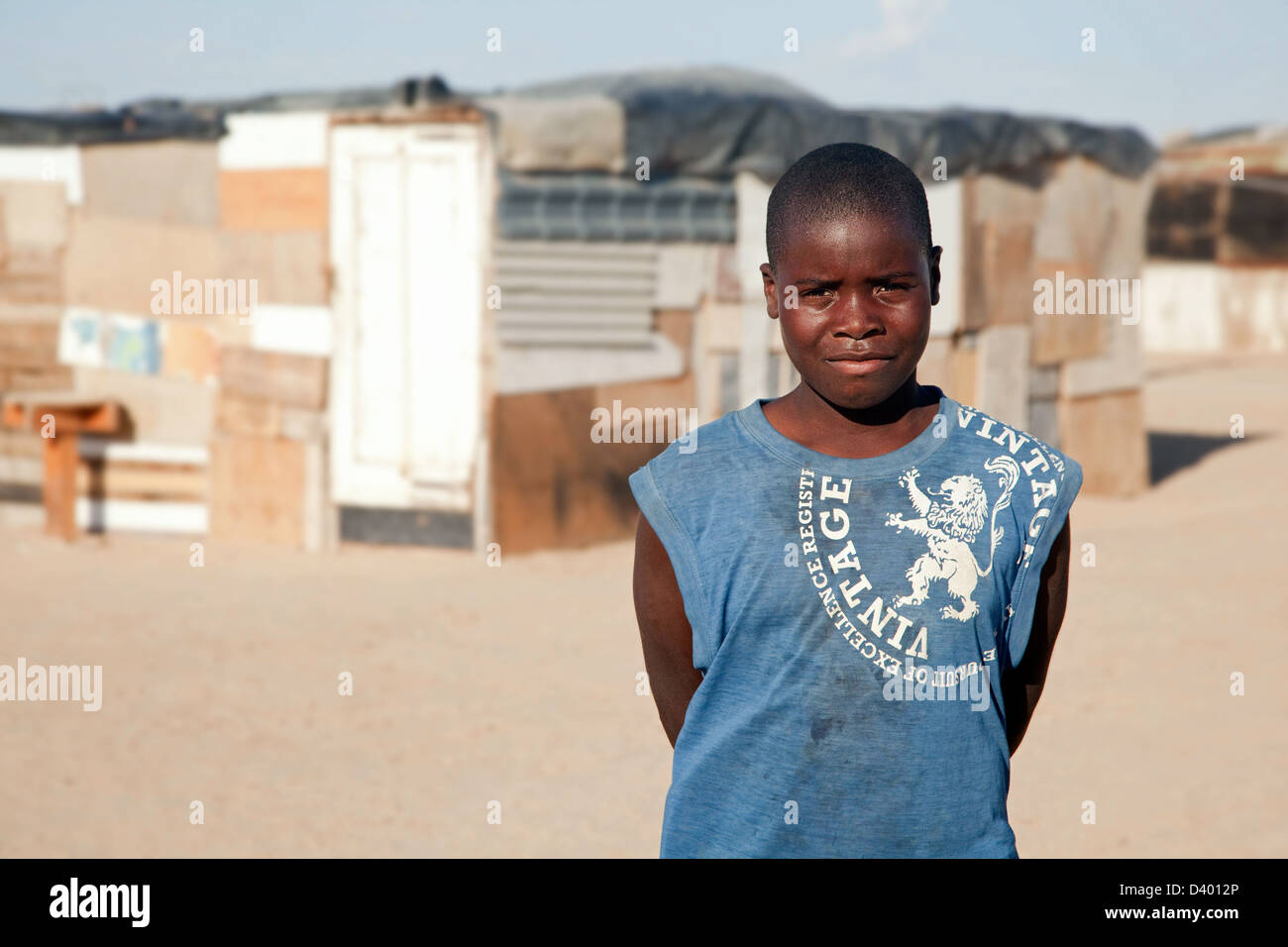 Teenager posing in front of improvised shacks, made from scrap materials at slum near Swakopmund, Namibia, South - Stock Image