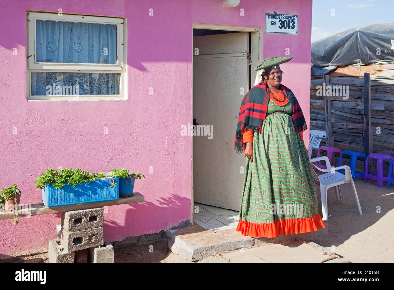 Herero woman in traditional colourful dress in front of her house in township near Swakopmund, Namibia, South Africa - Stock Image