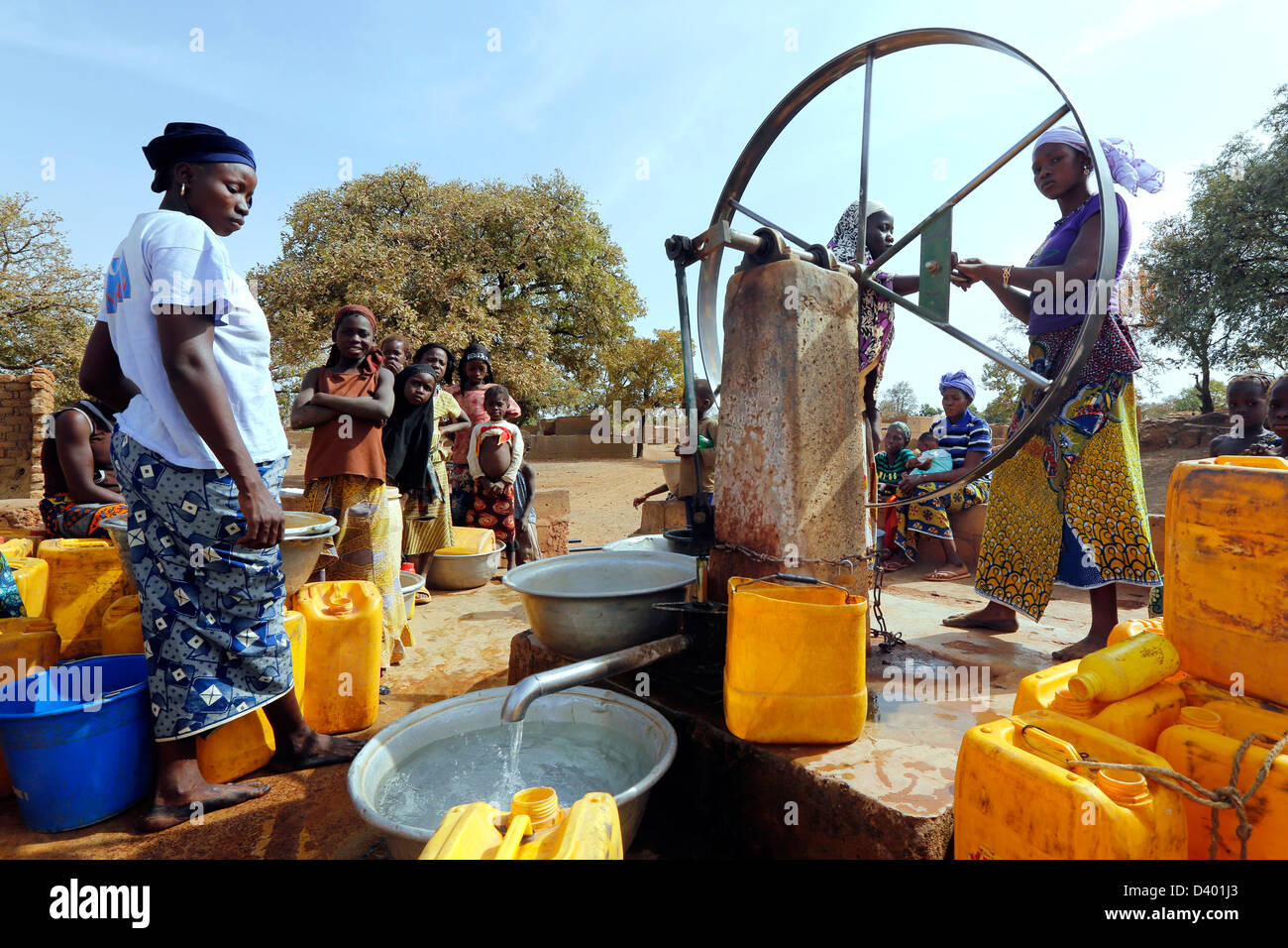 Women gather around the water pump of the village, Burkina Faso, Africa - Stock Image