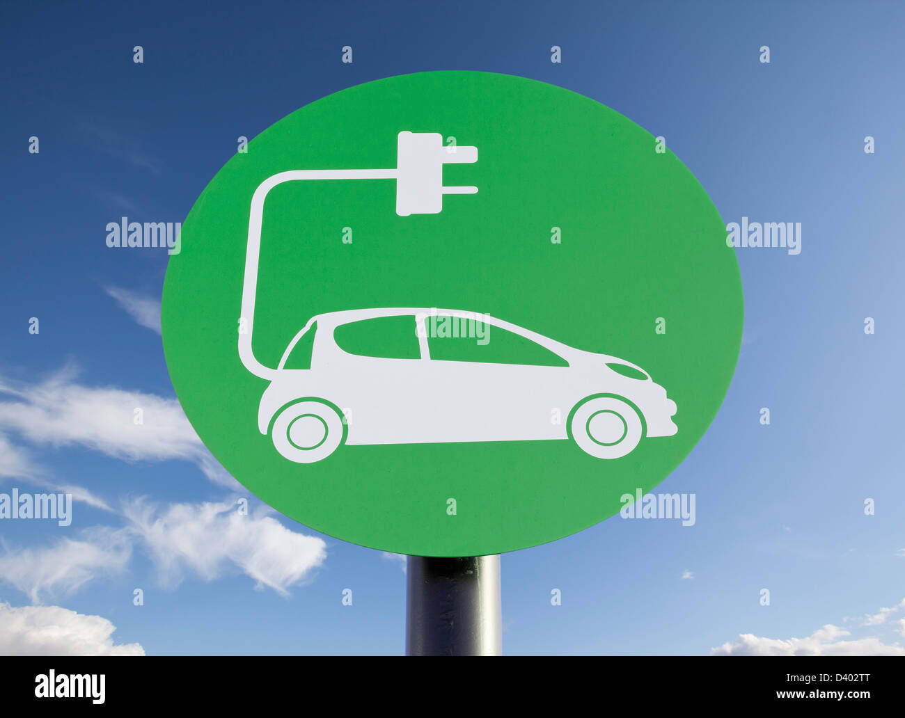 Green sign indicating a charging point for electric vehicles, sunny blue sky added in post-production - Stock Image
