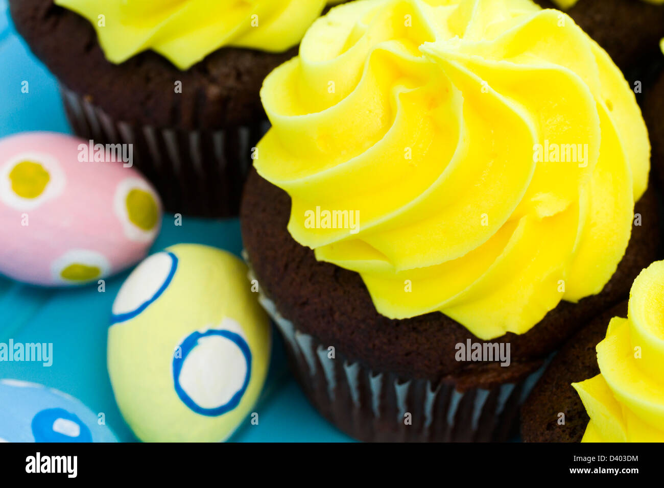Gourmet cupcakes with yellow icing prepared for Easter. - Stock Image