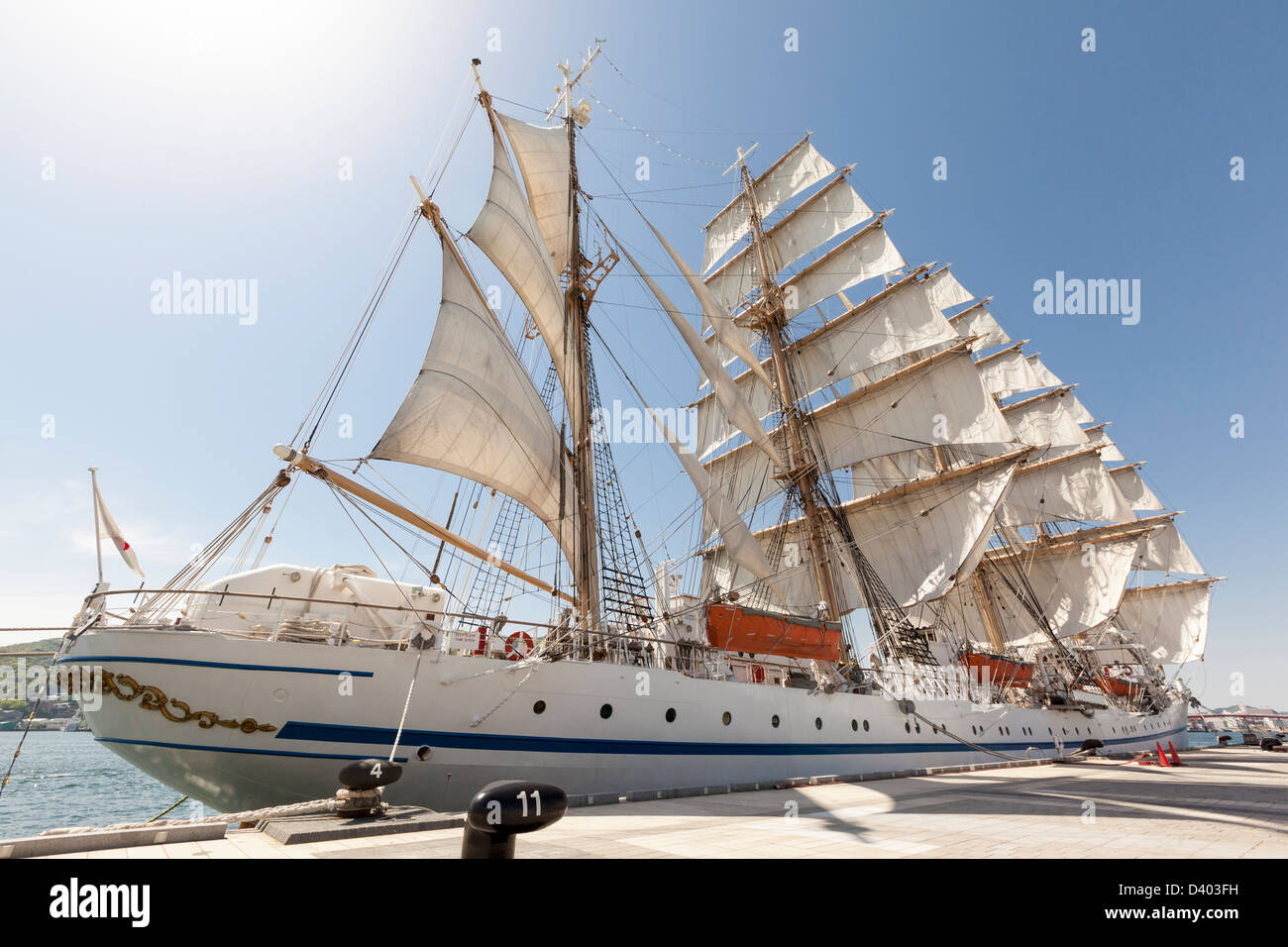 A tall ship, classified as a four masted barque, moored at Nagasaki docks with all sails set. - Stock Image
