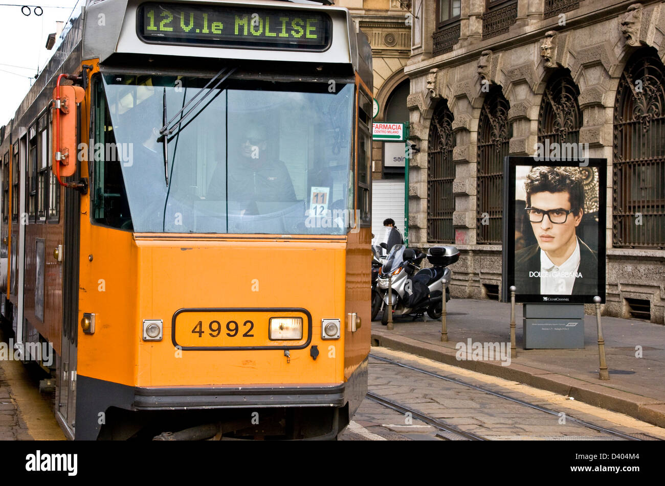 Yellow electric tram passing Dolce & Gabbana advert Milan Lombardy northern Italy Europe - Stock Image