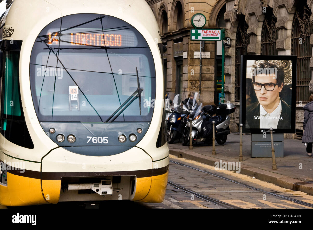 Street scene with modern electric tram passing Dolce & Gabbana advert Milan Lombardy Italy Europe - Stock Image