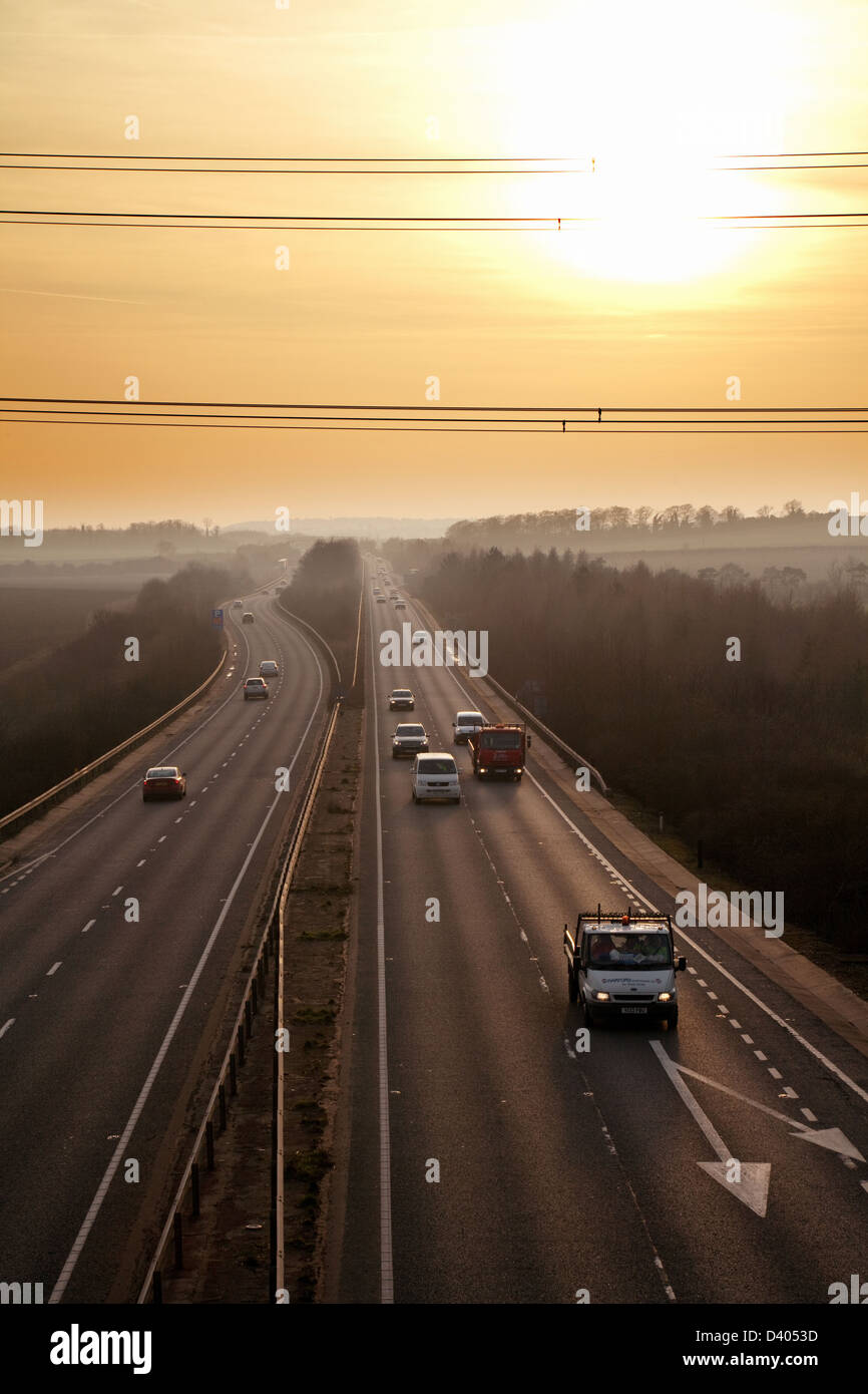 Cars driving on the A14  dual carriageway road in Cambridgeshire at sunset, England UK - Stock Image