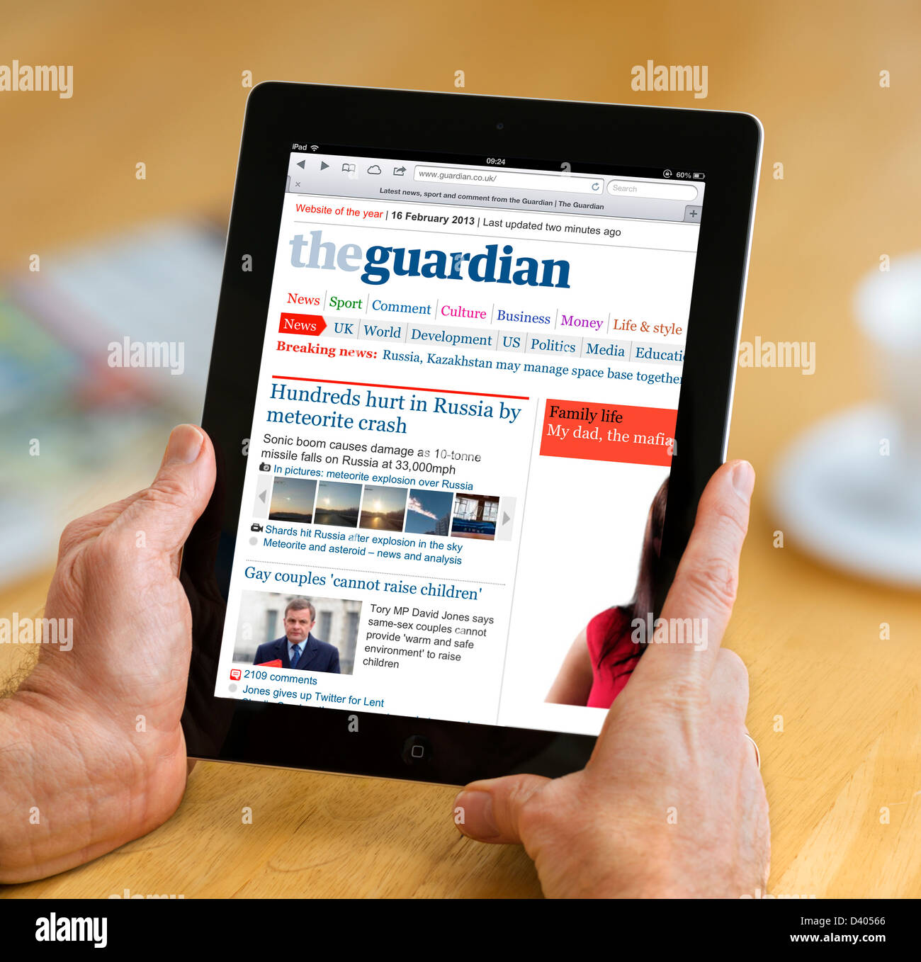 Reading the internet edition of the Guardian online newspaper on a 4th Generation iPad, UK - Stock Image