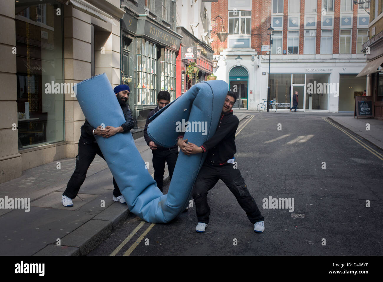 A Team Of Asian Workmen Manhandle Roll Industrial Carpet In Side Street And Destined For Nearby Shop Londons New Bond
