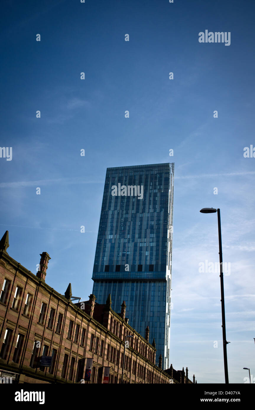 Street view of Manchester Hilton Tower enveloped in clear blue sky juxtapositioned against brick buildings - Stock Image