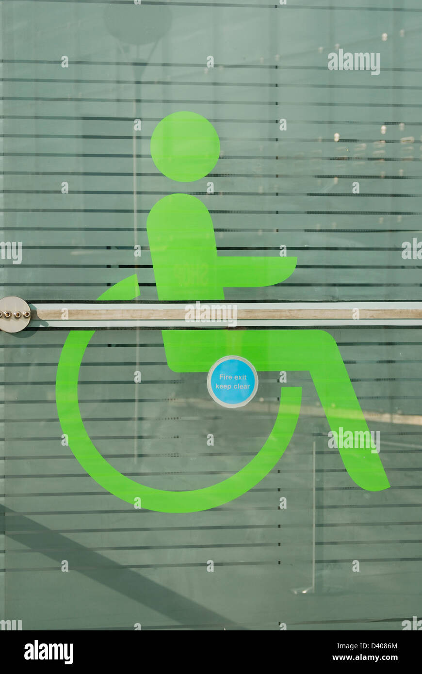 Disability sign on plate glass facade of the Urbis Building, Manchester. - Stock Image
