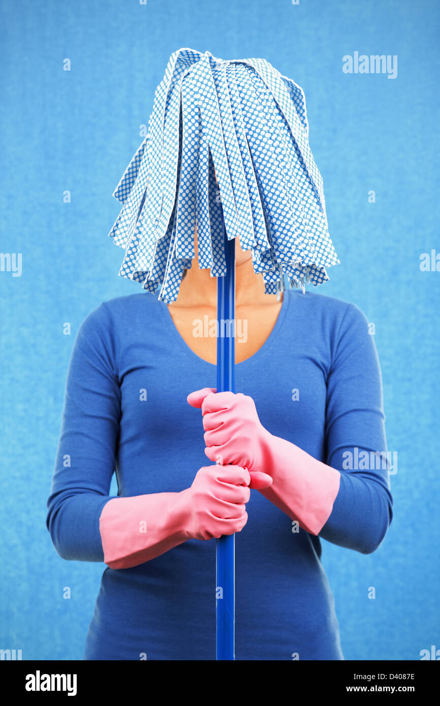 Young mixed race woman holding mop in front of her face isolated on blue background - Stock Image