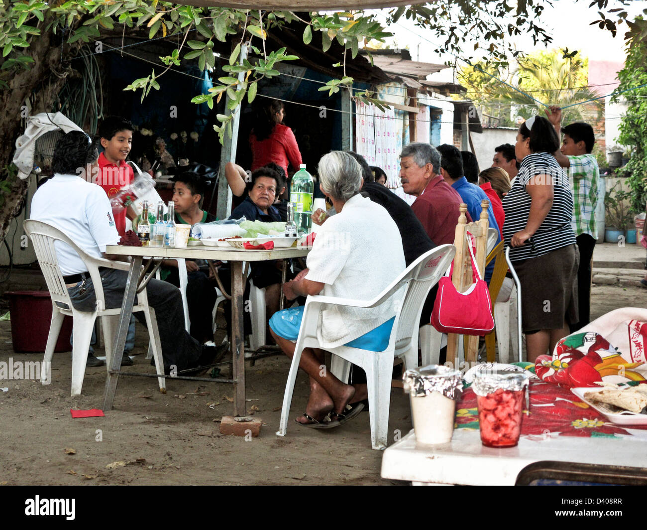 4 generations of a Mexican family enjoy Sunday afternoon comida meal together in courtyard of their home Oaxaca - Stock Image