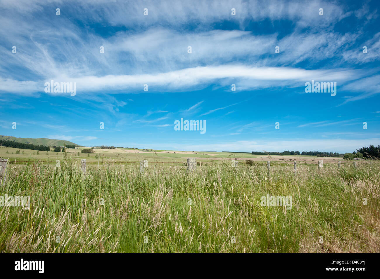 Cirrus high cloud being blown across a rural landscape. - Stock Image