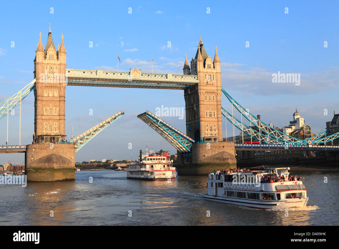 Tower Bridge open with pleasure cruise boat passing through, River Thames, London, England, UK, Britain, GB - Stock Image
