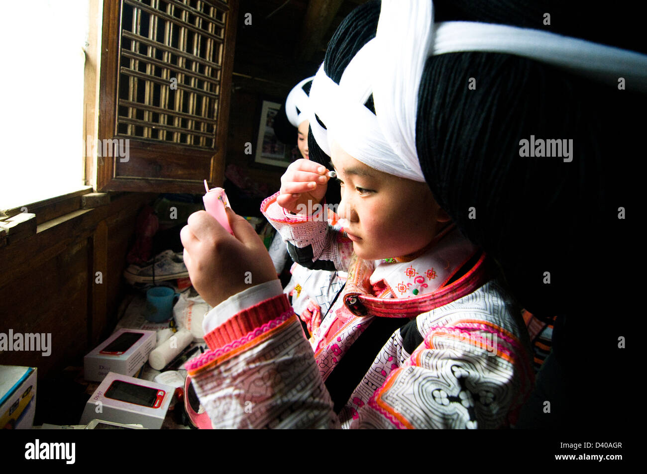 Long Horn Miao teenage girls getting ready for the Tiao Hua festival in Guizhou. - Stock Image