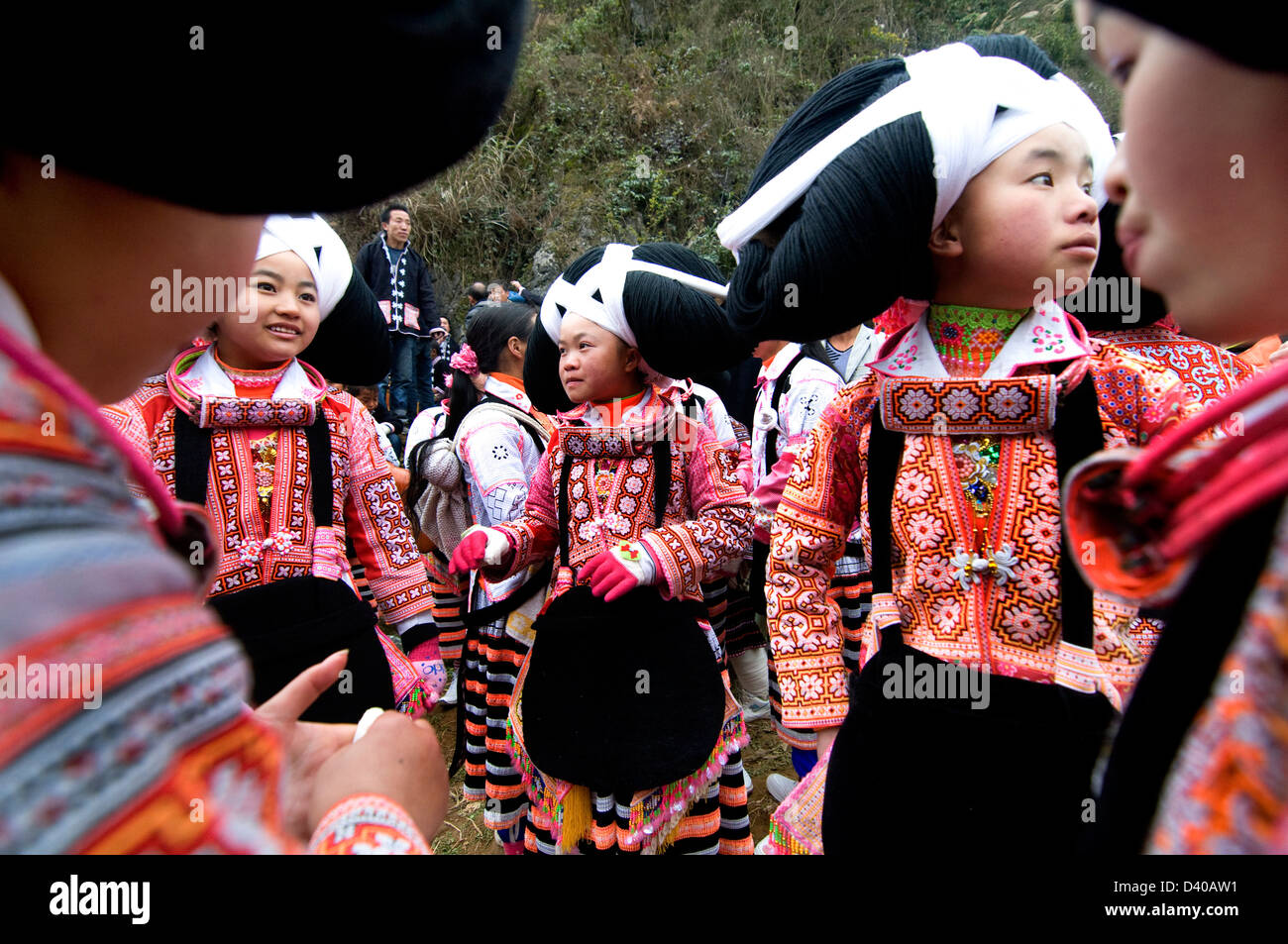 A Long Horn Miao little girl in traditional costumes dancing to celebrate the Tiao Hua festival / spring festival - Stock Image