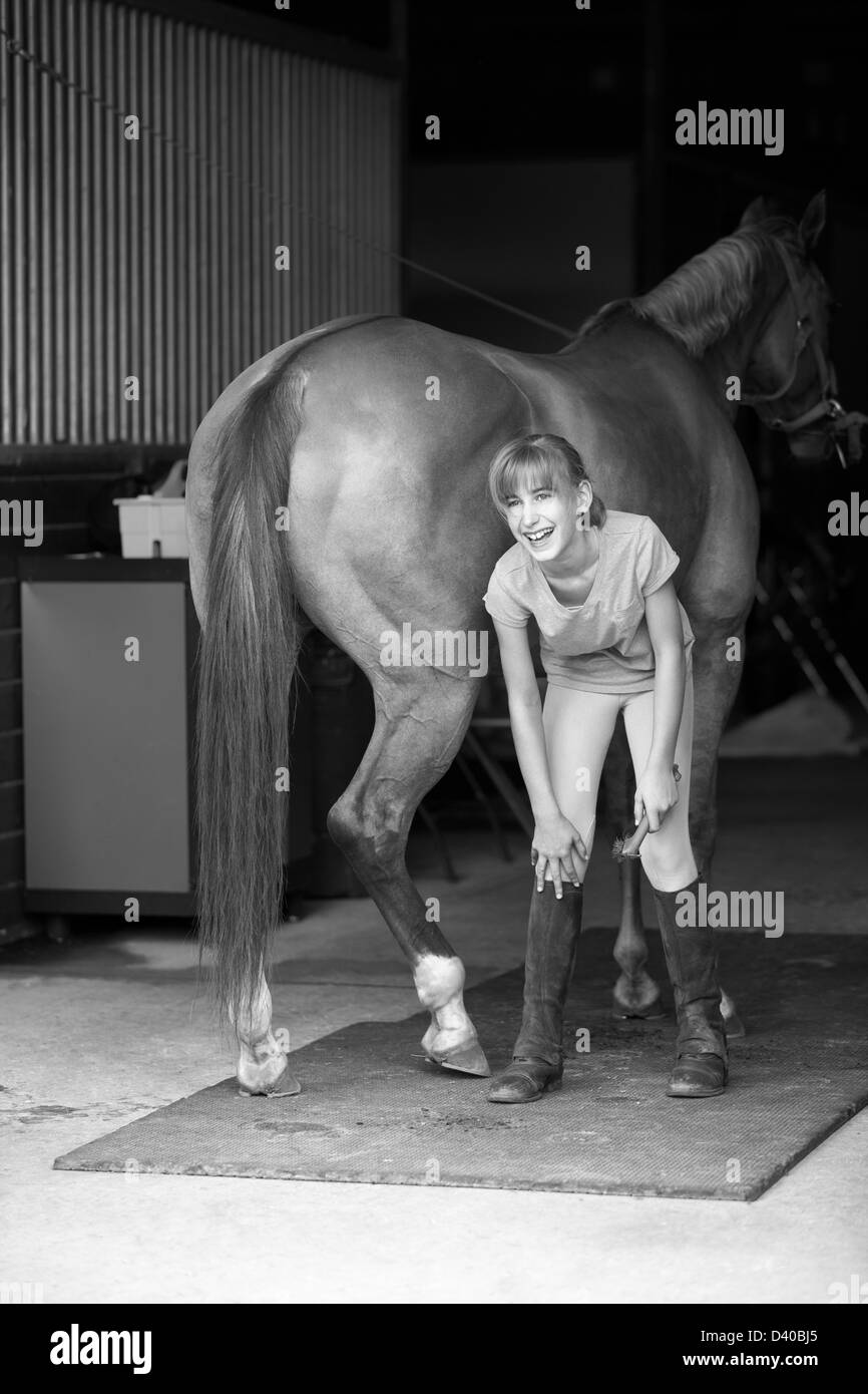 Beautiful smiling preadolescence female Caucasian child grooming her horse in a barn, grayscale black and white - Stock Image
