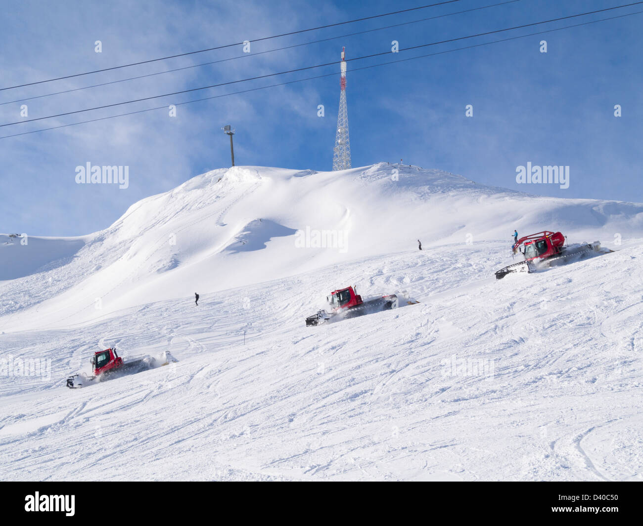 Snow bashers caterpillar tracked vehicles grooming the piste in St Anton, Tyrol, Austria, Europe - Stock Image