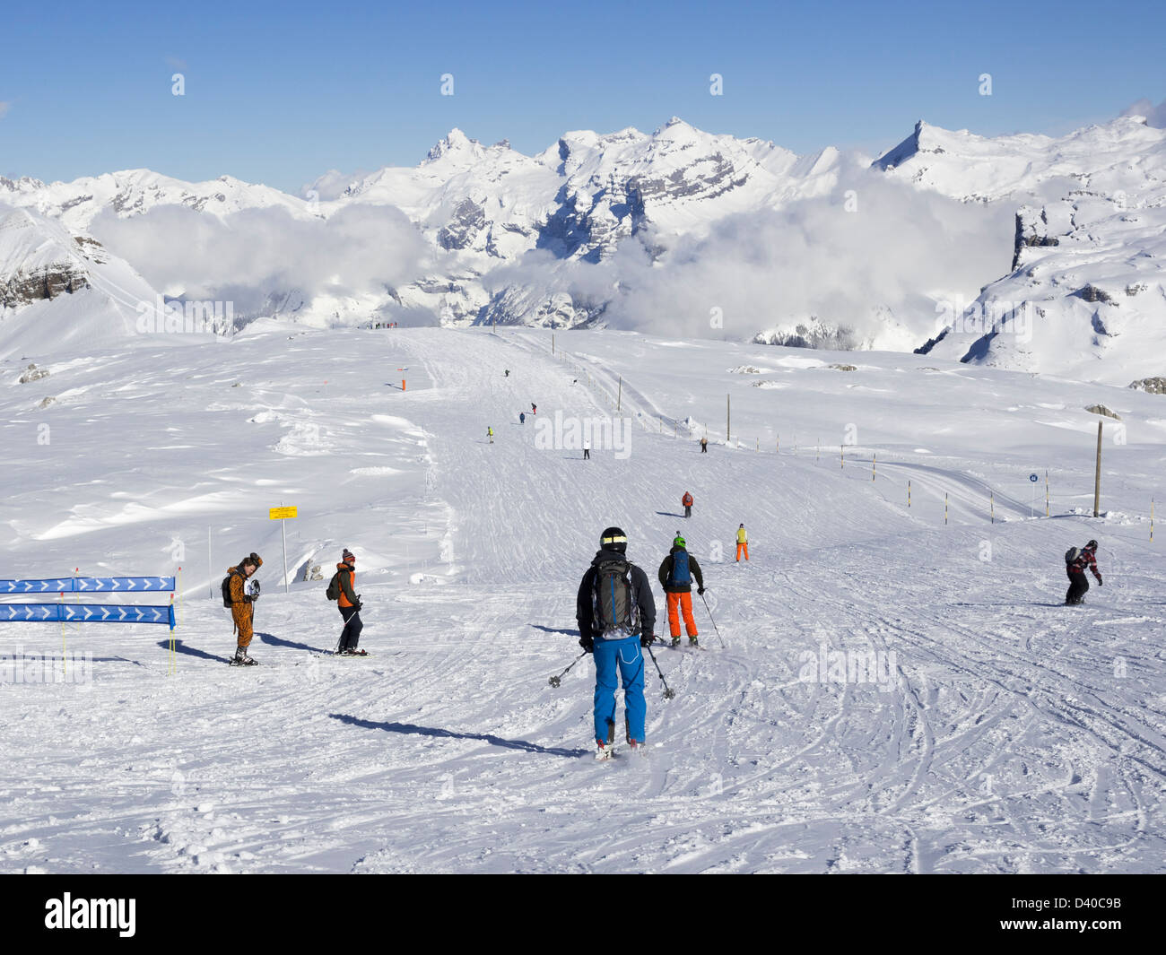 Skiers skiing blue run on Les Grandes Platieres in Le Grand Massif ski area with  mountains in French Alps. Flaine, - Stock Image