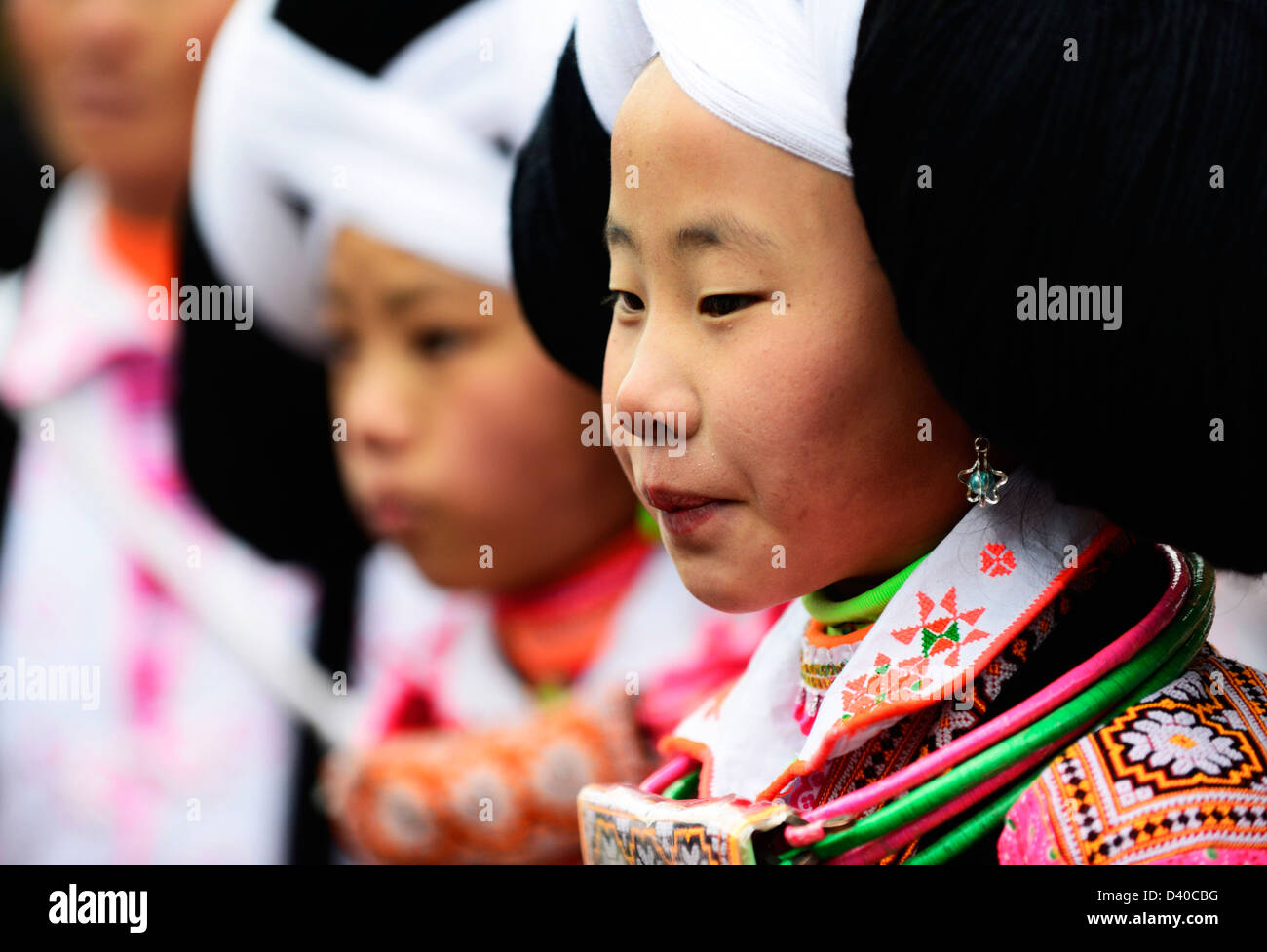 A Long Horn Miao little girl in traditional costumes dancing to celebrate the Tiao Hua festival / spring festival Stock Photo