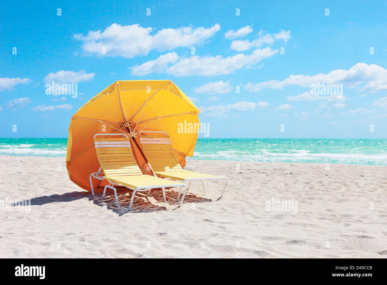 A Pair Of Sunbathing Chairs And Beach Umbrella