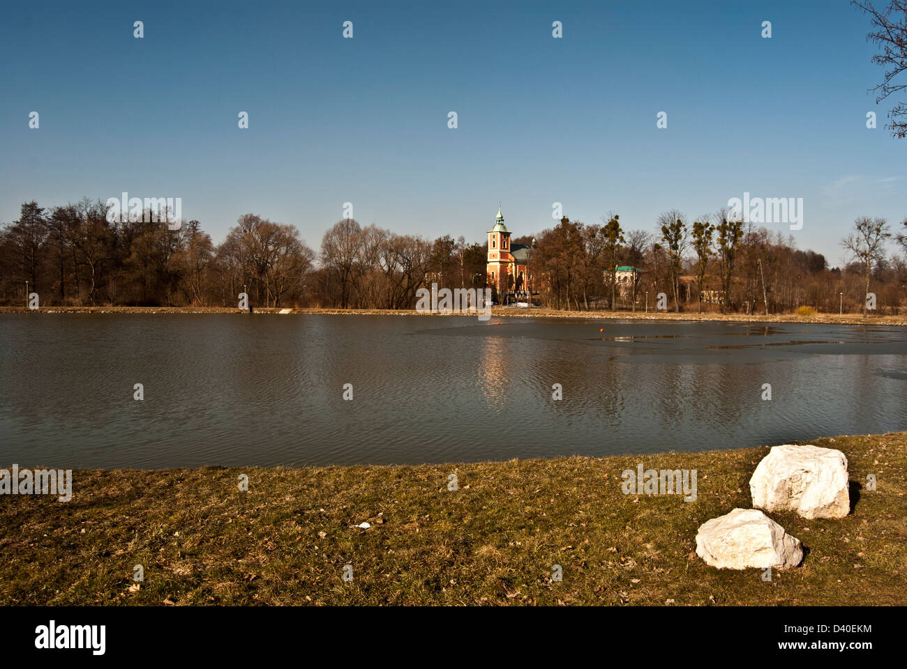 Navesni rybnik pond with Bohuslavice villagw with Kostel Nejsetejsi Trojice church and clear sky near Ostrava city - Stock Image