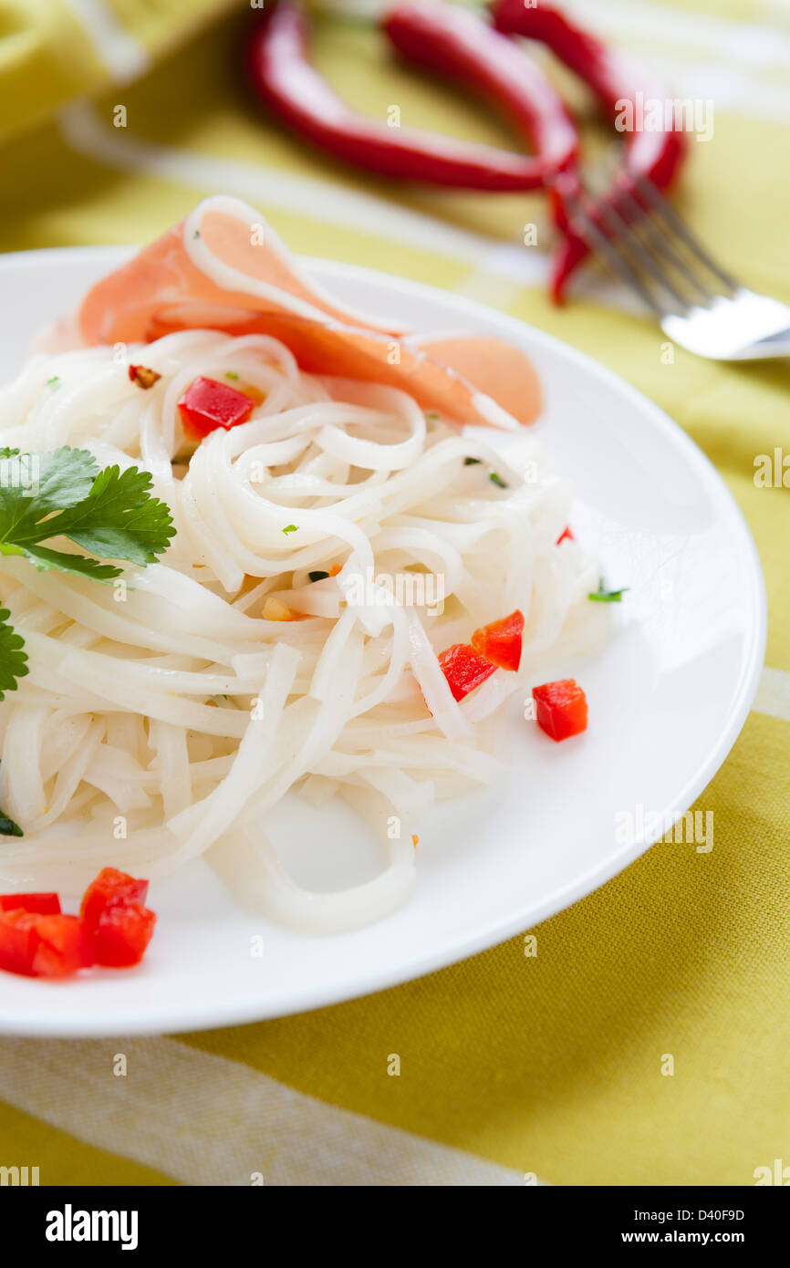 rice noodles with cilantro on a white plate, closeup Stock