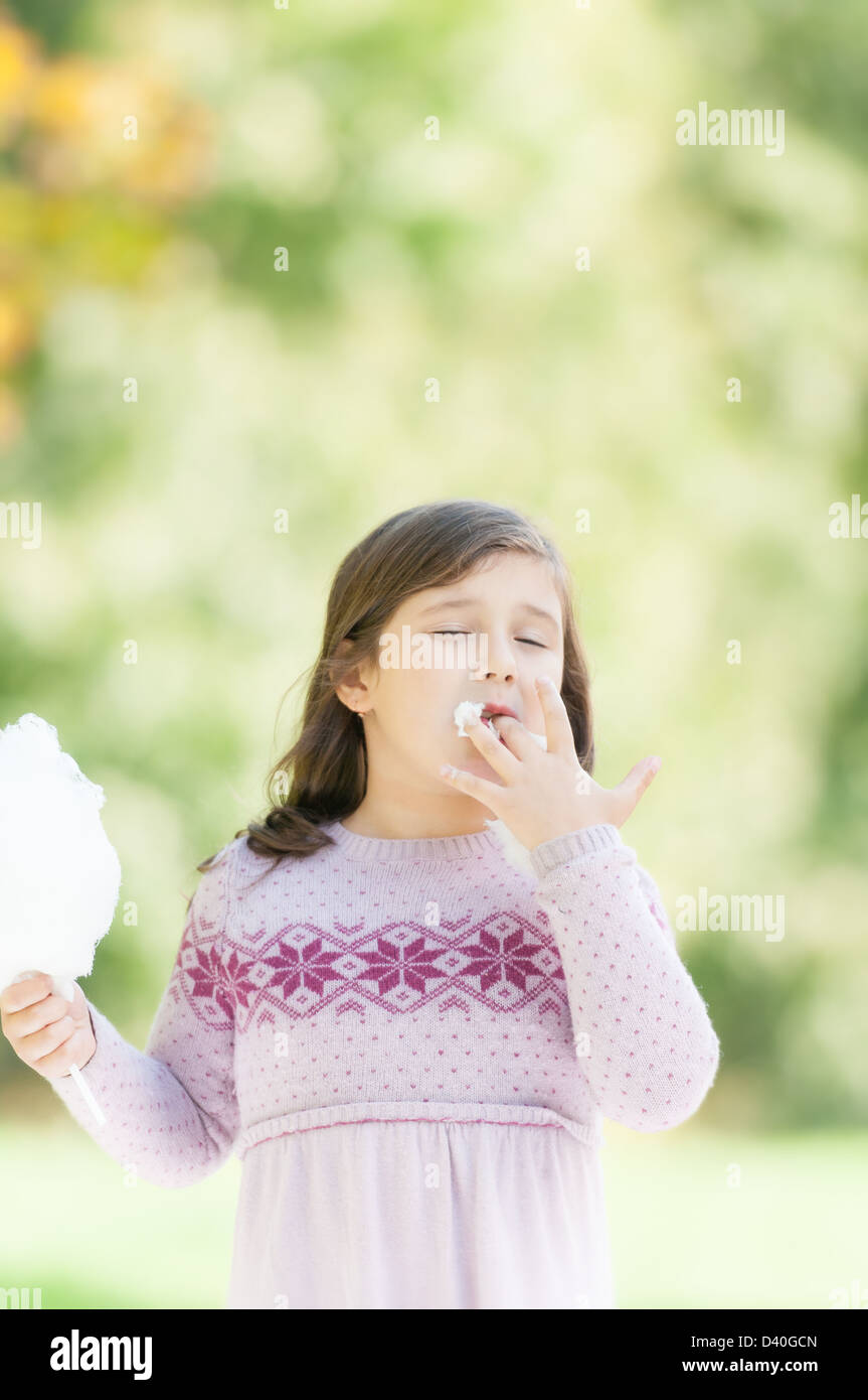 cute kid in purple dress eating candyfloss. child licking fingers