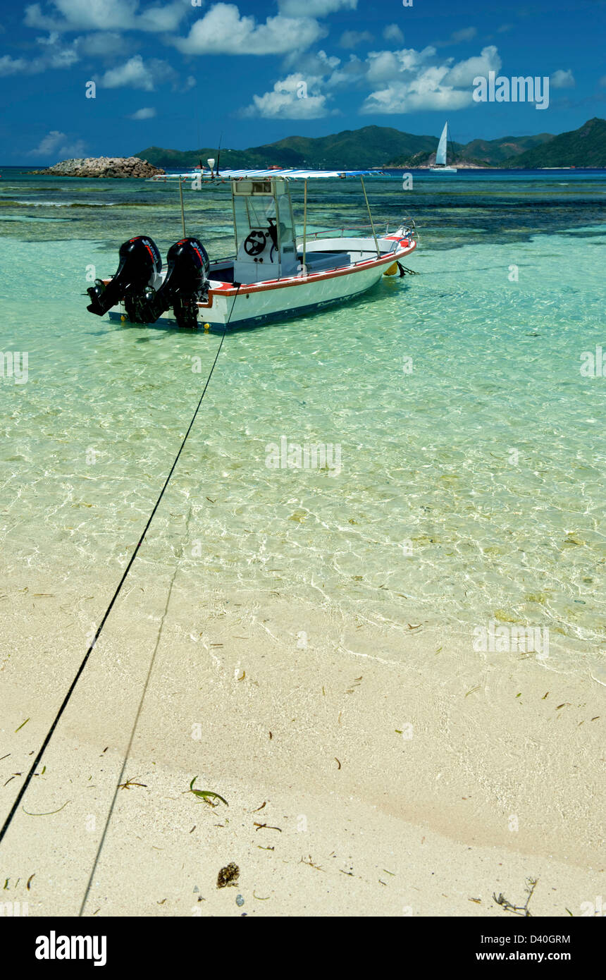 A boat on the beach of La Dique in the Seychelles - Stock Image