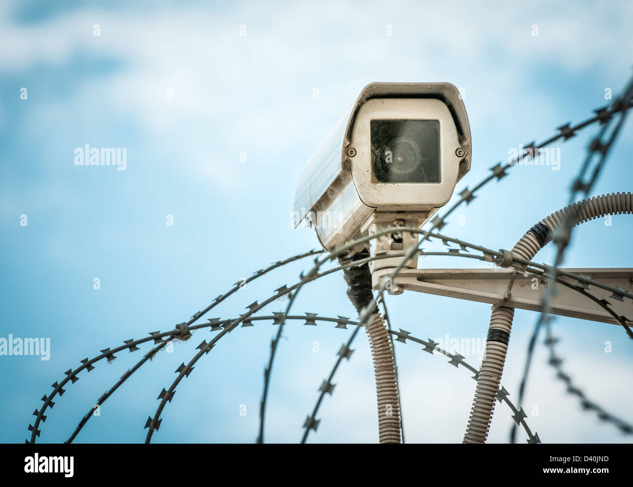 Close up view of security camera hanging among barbwire in prison or other guarded object with blue sky background. - Stock Image