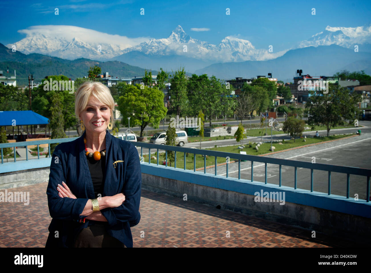Joanna Lumley at Pokhara Airport, with Annapurna mountains behind - Stock Image