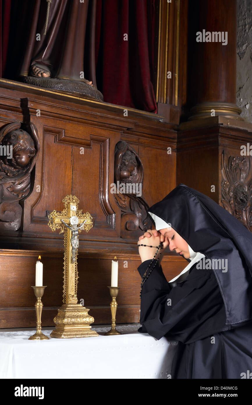 17th century chapel of a medieval church and a young novice in prayer Stock Photo