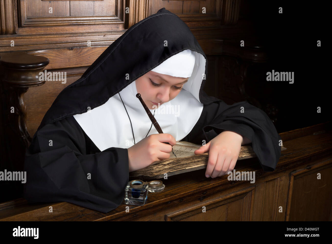 Young nun writing in an ancient book in a medieval church interior - Stock Image