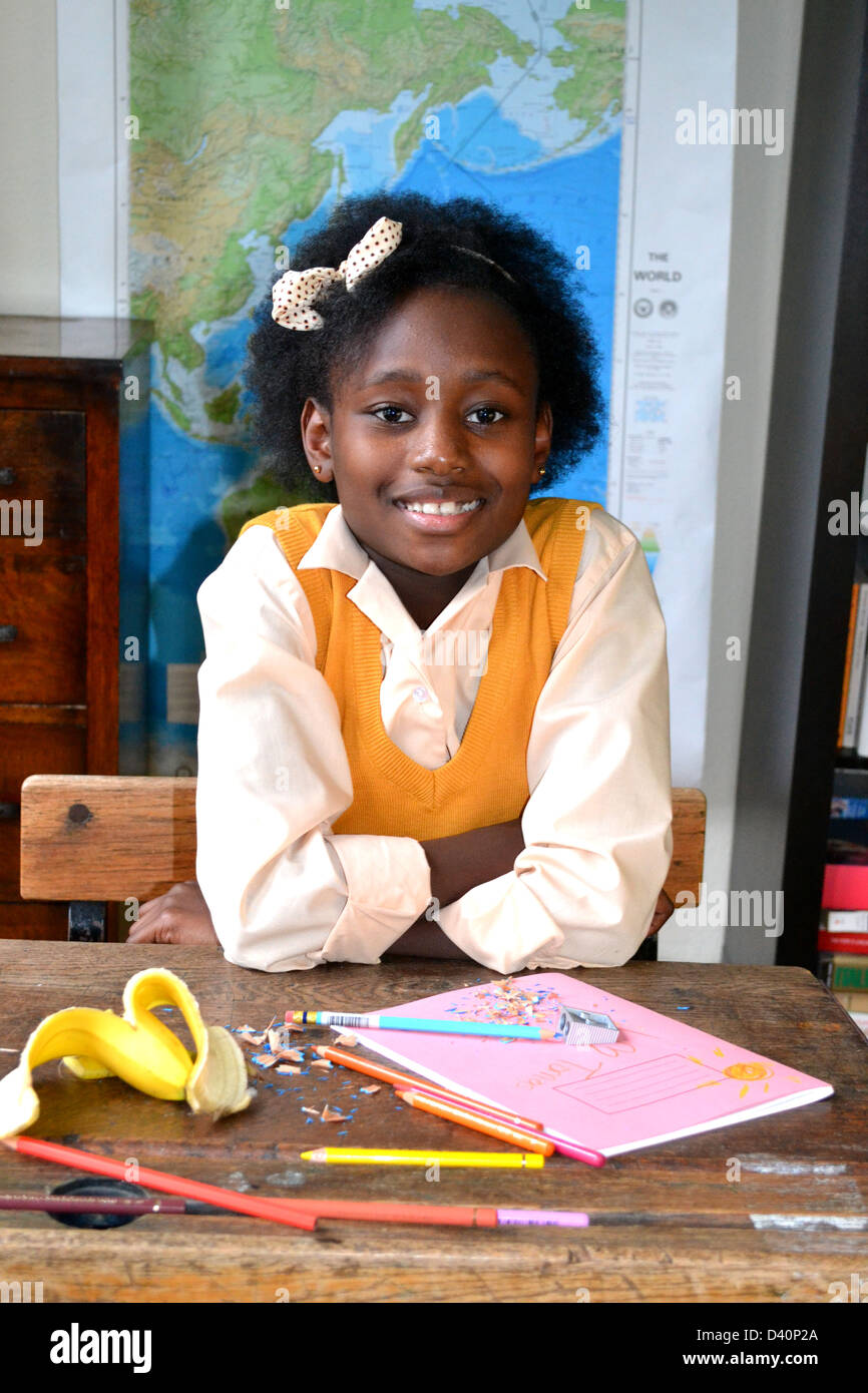Sweet smiling little girl sitting at an untidy desk in a classroom. - Stock Image