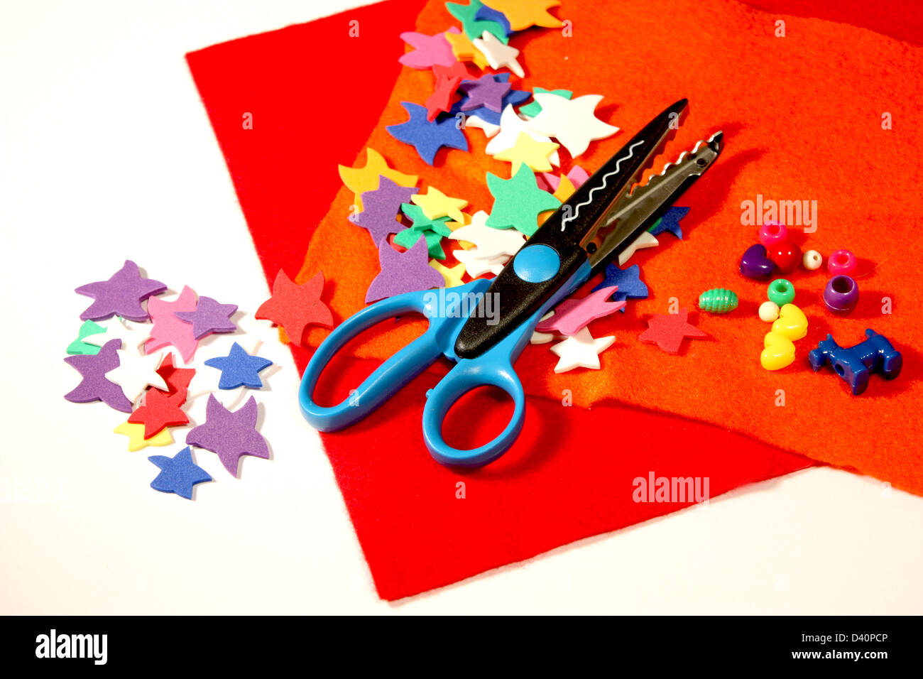 Arts and crafts felt with cutouts and scissors on white background - Stock Image