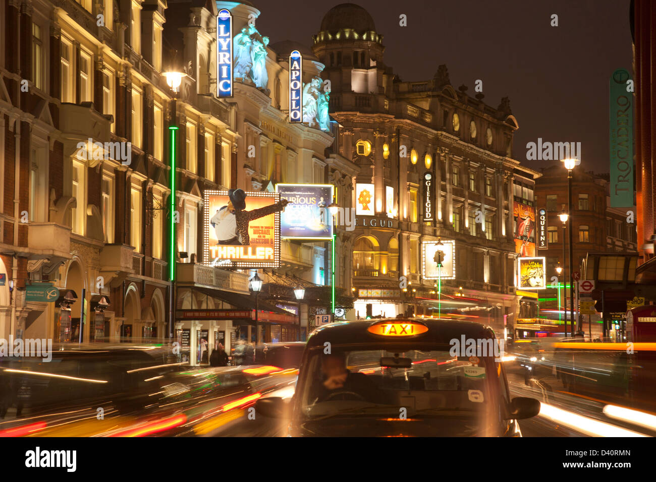 Heart of London theatreland, Shaftesbury Avenue: Lyric, Apollo, Gielgud, Queens theatres with taxi in foreground - Stock Image