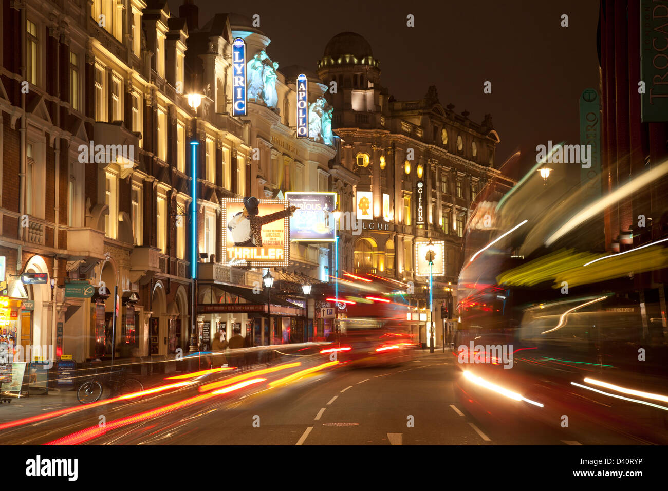 Heart of London theatreland, Shaftesbury Avenue: Lyric, Apollo, Gielgud theatres with bus light trails at night - Stock Image