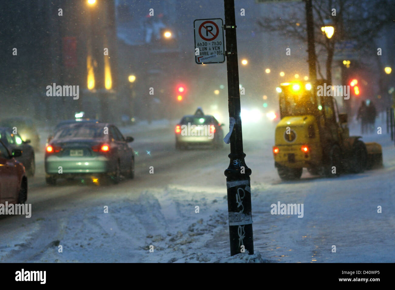 Sidewalk snow removal during rush hour in Montreal, Quebec during a heavy snowfall. - Stock Image
