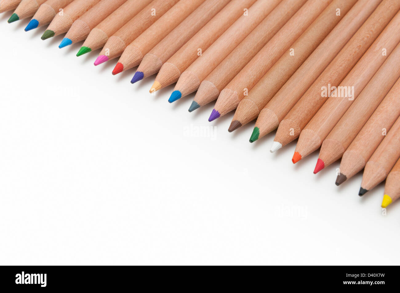 Line of coloured pencils on a white background - Stock Image