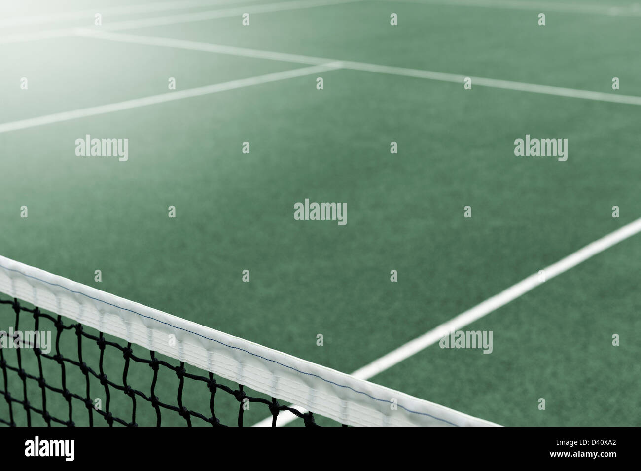 View of a Tennis Court with the net in the foreground - Stock Image