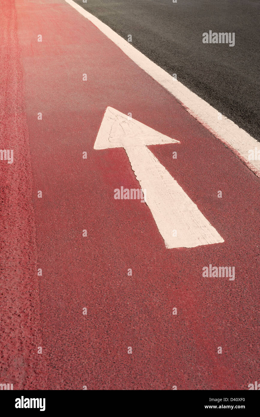 White straight ahead one way direction arrow road markings painted on a red road surface, UK - Stock Image
