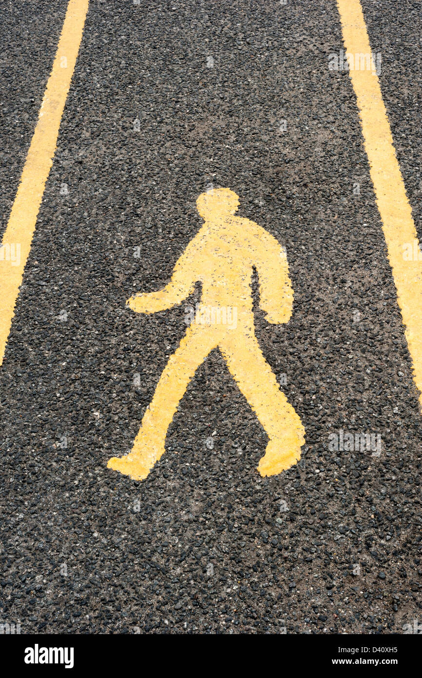 Yellow pedestrian road safety walkway sign painted a road in a car park, UK - Stock Image