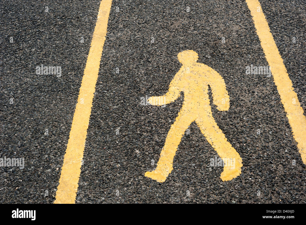 Pedestrian safety walkway sign / man symbol painted on a road surface in a car park, UK - Stock Image