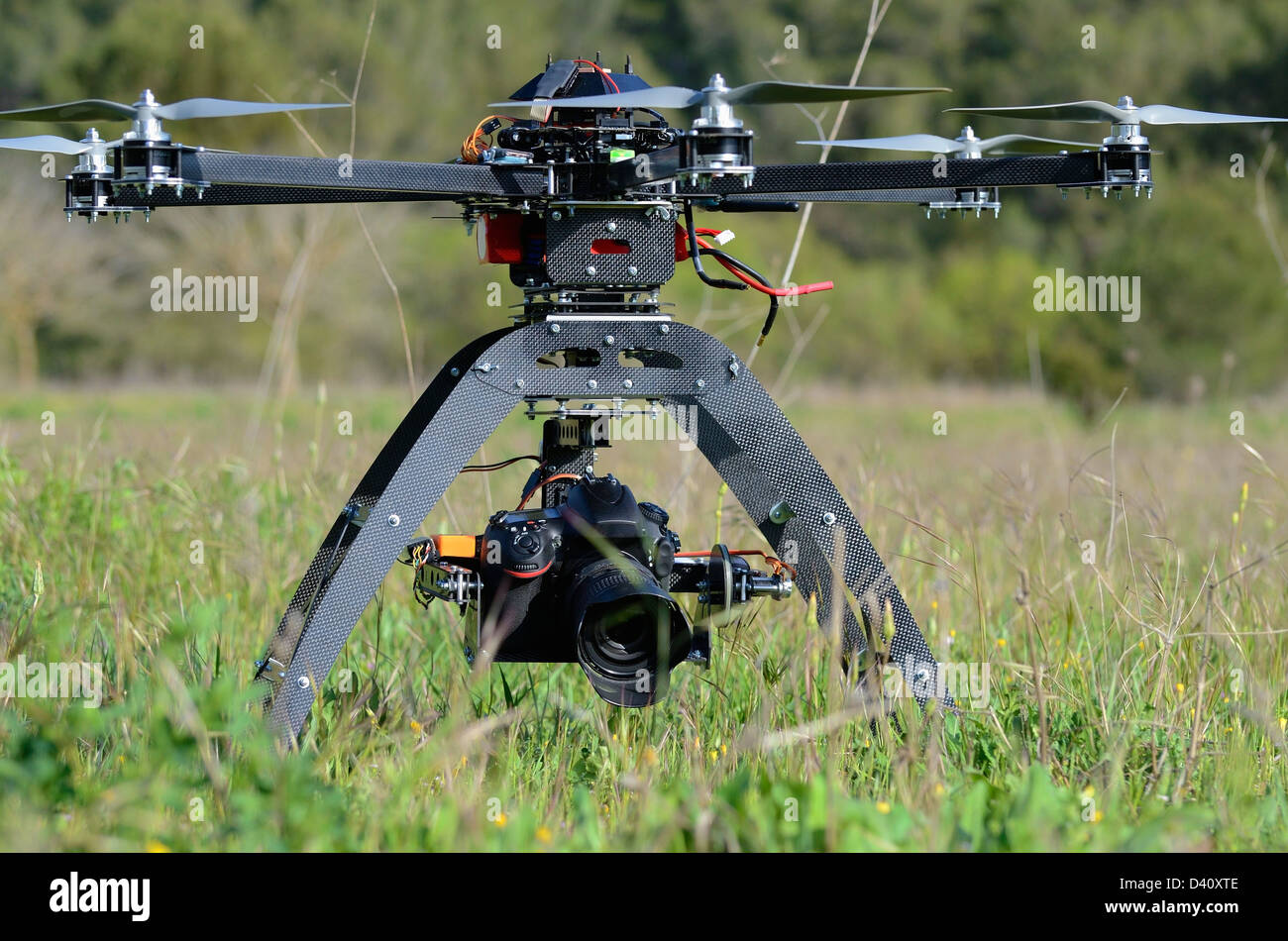 Drone and digital camera on an Unmanned Aerial Vehicle (UAV or Drone), with six rotors, used here for aerial photography - Stock Image