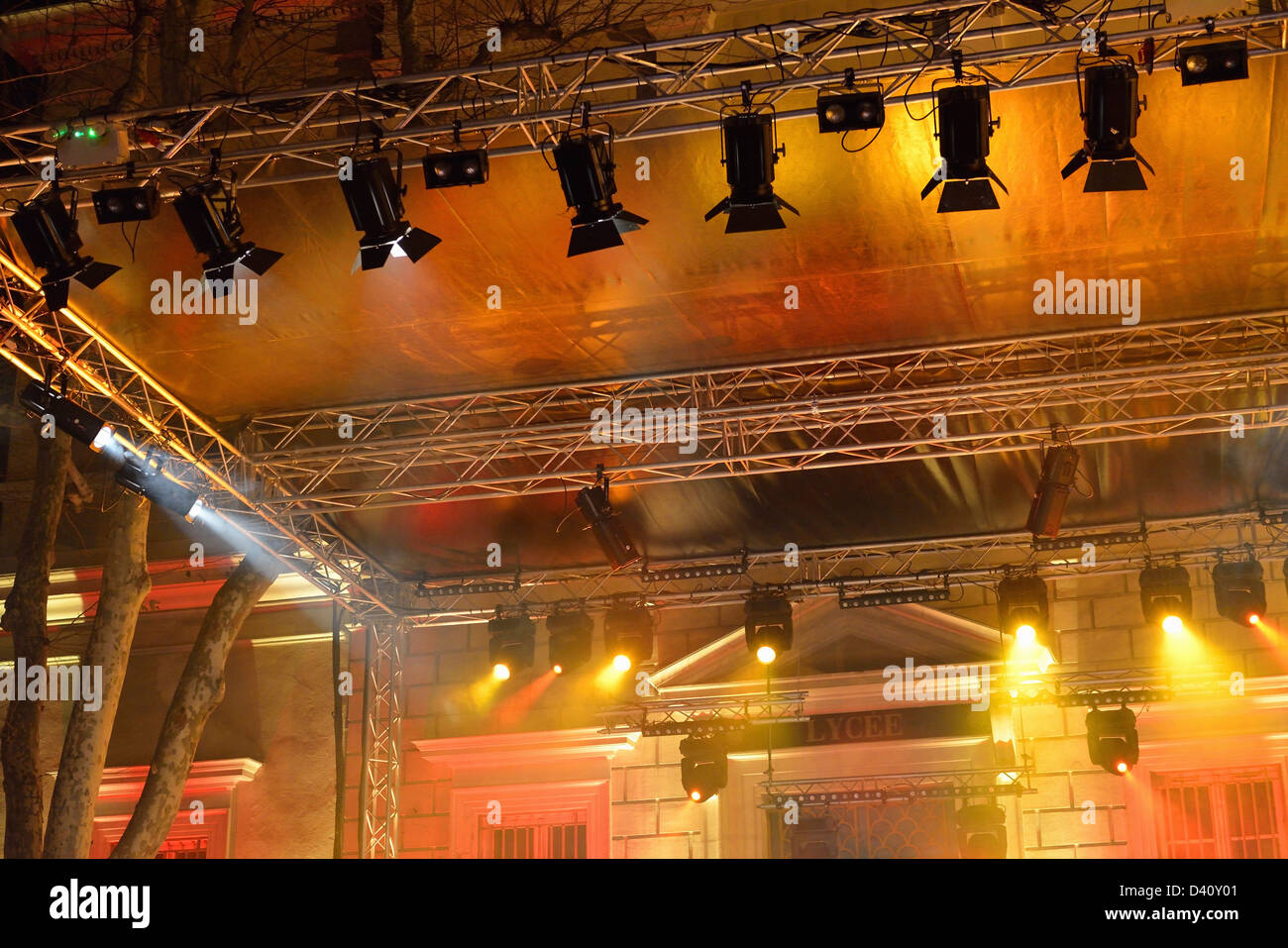 Colourful spotlights hanging on a rig on a batten above stage during a performance - Stock Image