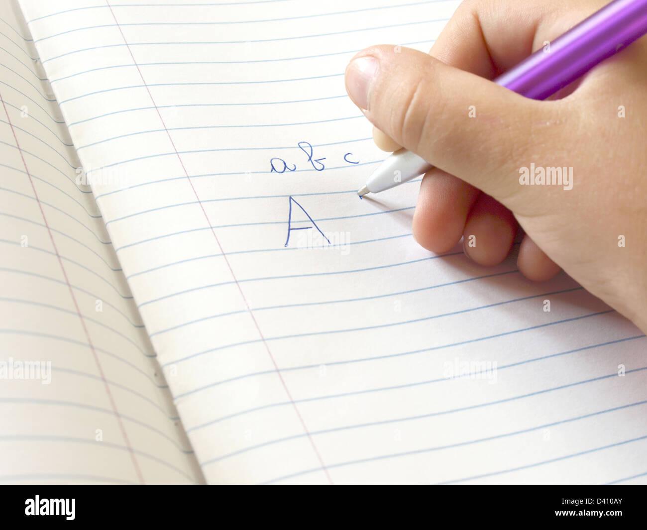 little hand writing homework on exercise book - Stock Image