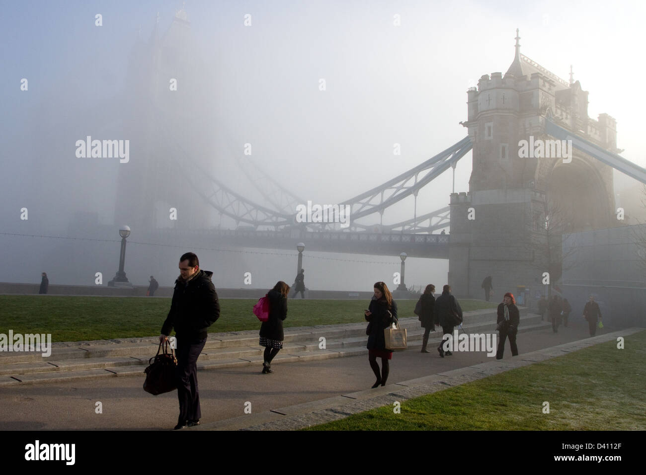 A picture shows commuters walking by Tower bridge through heavy fog and low cloud in London. - Stock Image