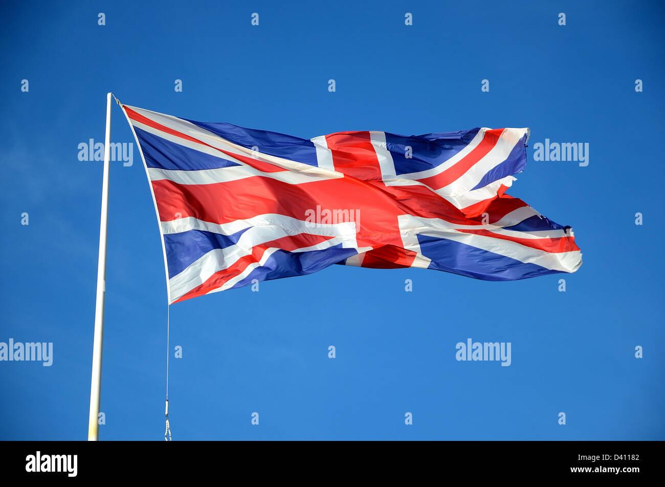 British Union Jack flag fluttering on flagpole - Stock Image