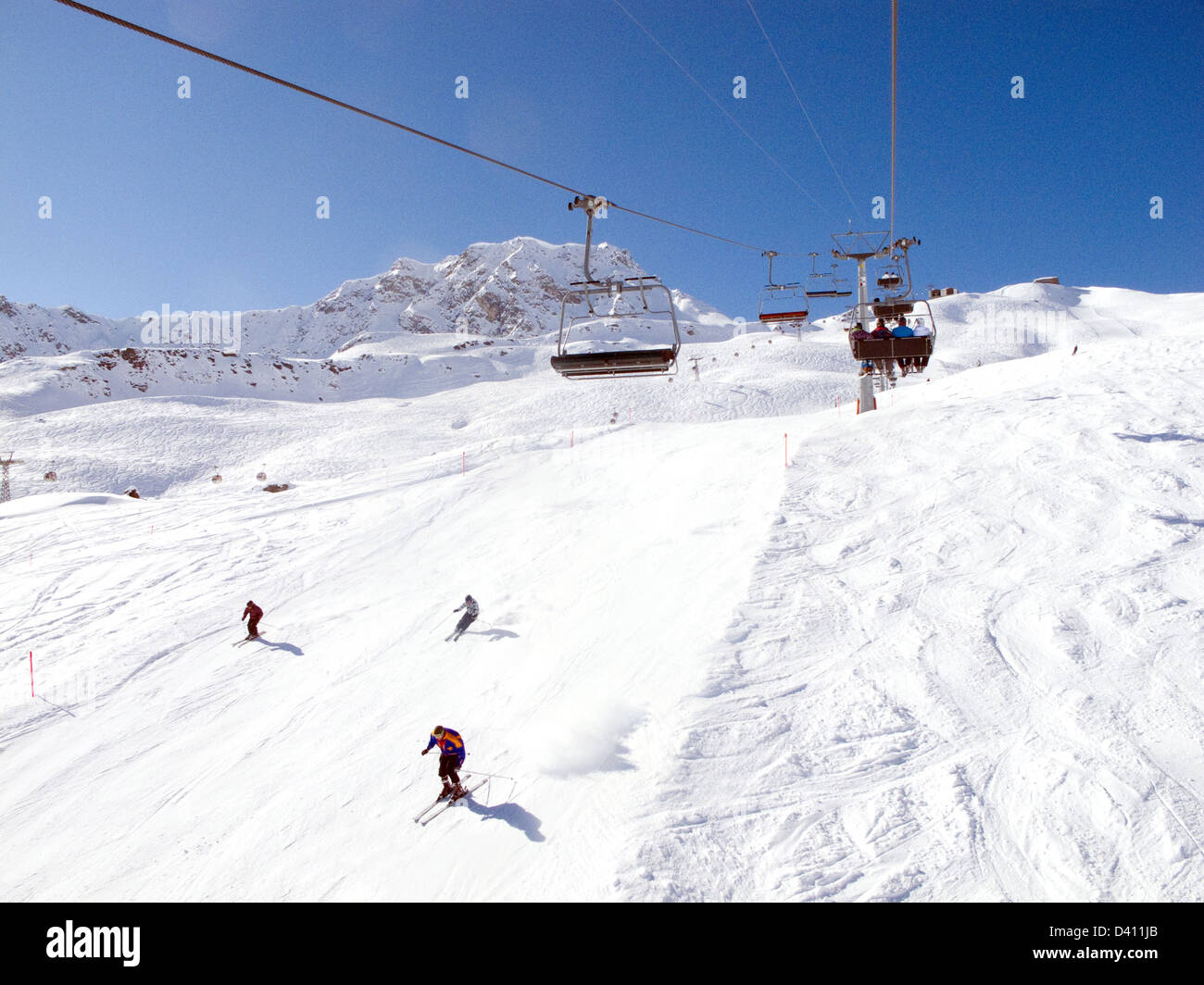 Skiers skiing on the slopes ( piste ), and the Hornli chairlift, Arosa ski resort Switzerland Europe - Stock Image