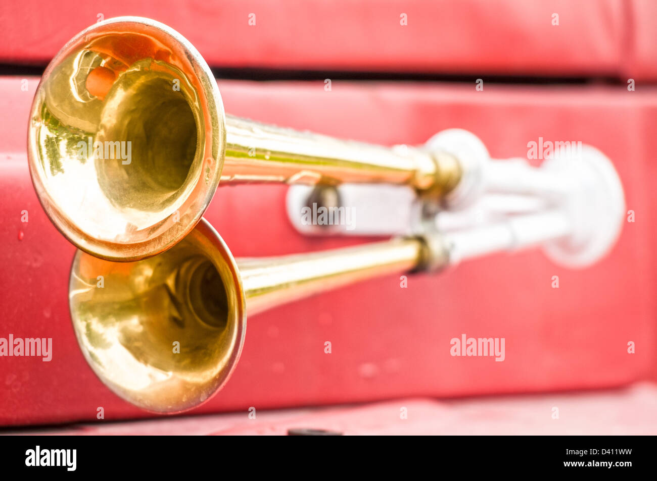 Close up view of two shiny metal horns on red firefighter car. Sound signal used to avoid traffic accidents. Way - Stock Image